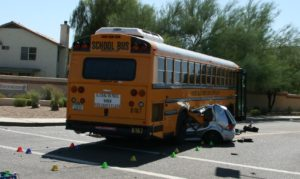 Car crushed by school bus, example of turing accident